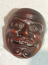 A late 19th century Japanese carved wooden netsuke Modelled as a figural mask.  5.75 cm high.