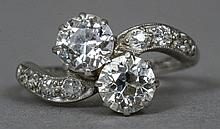 A platinum and diamond crossover ring The twin claw set stones flanked by diamond set shoulders.