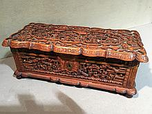 A late 19th/early 20th century Cantonese carved wooden box With hinged lid, carved throughout with figures and pagodas in a landscape.  16.5 cm wide.