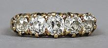 An 18 ct gold diamond five stone ring The claw set stones above incised shoulders.