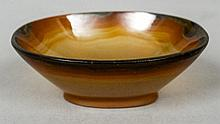 A small carved agate pedestal bowl Of oval form.  9 cm wide.