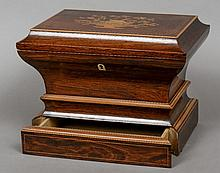 A 19th century French marquetry inlaid rosewood sewing box The domed hinged rectangular top inlaid with an urn of flowers enclosing a mirror and recess, the base with a plinth drawer.  38 cm wide.