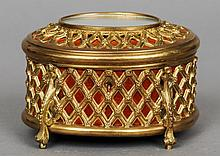 A 19th/20th century gilt metal casket by Tahan, Paris The oval hinged cover set with a mirror, the body with applied trellis work, standing on scroll feet, remnants of mark to lock plate.  15 cm wide.