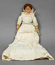 A 19th century wax headed doll In original costume, the arms and legs also wax.  39 cm long.