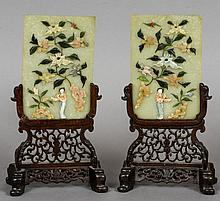 A pair of Chinese jade and hardstone table screens Each decorated with a female figure amongst floral scrollwork and a bird, each mounted on a carved and pierced wooden stand.  Each 26 cm high overall.  (2)
