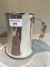 An early 20th century American Sterling silver Arts & Crafts quart tankard Of waisted form, with a serpentine rim and scrolling loop handle.  14.75 cm high.
