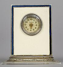 An enamel decorated silver miniature desk clock With cream and blue enamel decorations, the circular dial inscribed Usita.  3.75 cm high.