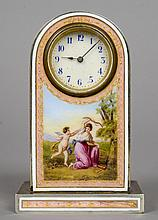 A pink enamel decorated desk clock The white circular dial with Arabic numerals above a figural vignette depicting cupid.  9.5 cm high.