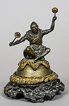 A 19th century patinated bronze table bell Modelled as a  native figure seated on an animal skin above the naturalistically cast base.  22 cm high.