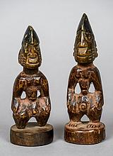 A pair of small Yoruba tribal figures Each modelled standing on a circular plinth base.  The largest 18 cm high.  (2)