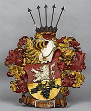 A carved and painted wood heraldic crest The shield worked with a lion and fruiting vine mounted arrow, surmounted with a helmet issuing five further arrows and flanked with scrolling acanthus above a ribbon inscribed Bastion.  62 cm wide.