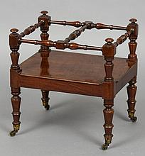 An unusual Victorian mahogany Canterbury The twin sections divided with turned stretchers above a plain frieze, standing on turned legs with brass caps and castors.  47 cm wide.