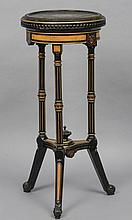 A 19th century ebonised and amboyna jardiniere stand The circular top with gilt brass beading above the tablet inset frieze, standing on three reeded legs united with an undertier.  44 cm diameter.