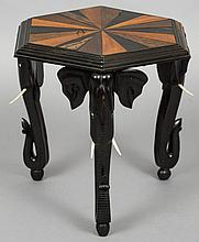 A 19th century Anglo-Indian specimen wood side table The hexagonal shaped top inlaid with various specimen woods, standing on carved ebony elephant mask legs.  46 cm wide.