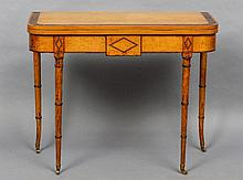 A 19th century birdseye maple card table The crossbanded hinged folding rounded rectangular top above a lozenge inlaid frieze, standing on turned tapering legs with brass caps and castors.  90.5 cm wide.