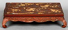 A 19th century Chinese cinnabar lacquered low tea table Of rectangular form, decorated with figures and pagodas amongst a mountainous landscape above the florally decorated shaped apron, standing on scrolling feet.  52 cm wide.