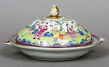 A 19th century Cantonese famille rose warming dish and cover Of typical form, decorated with figures in a garden.  24 cm diameter.