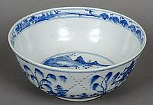 A Chinese blue and white porcelain bowl Decorated with figures and pagodas in a continuous landscape, blue painted four character Kangxi mark to base.  26 cm diameter.