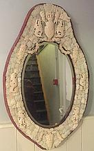 A 19th century Dieppe carved ivory wall mirror The oval bevelled plate bordered with figural masks, rampant lions and stylised dolphins and surmounted with a crest inscribed Lavsdeo.  91 cm high.