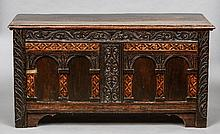A 17th century  and later specimen wood inlaid oak coffer With carved and arched panel front.  129 cm wide.