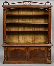 A Victorian oak Gothic Revival standing bookcase The rectangular top with a pierced back rail centred with a quatrefoil, above the shelved section flanked by quatrefoil headed panels, above twin panelled doors standing on a plinth base.  130 cm wide.