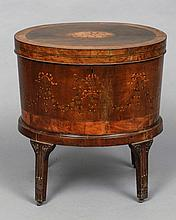 A George III mahogany and satinwood marquetry inlaid oval cellaret and stand The oval hinged top inlaid with a patera above ribbon tied berried husk swag inlaid body, the stand with stop fluted legs with brass castors.  61 cm wide.