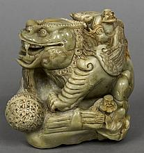 A Chinese carved soapstone group Worked as figures attending an oversized m