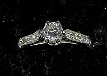 A platinum and diamond solitaire ring The central