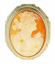 Shell cameo pin with carving of a young woman in profile, set in a 14 karat white gold frame with engraved border, 1 1/4
