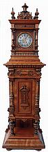 Lenzkirch, Germany, Symphonion Hall Clock, style No. 25 St., walnut case with heavily molded base and standing on compressed ball feet, richly ornamented with veneers, turned elements and carving, mid section with door concealing the music player and