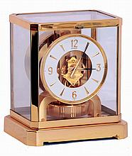Jaeger- LeCoultre, Switzerland Atmos clock, cal.528-8, gilt, rectilinear glazed case, the base with cotes de Geneve decoration, Arabic numeral and arrow marker white painted dial, gilt hands with black tips, 15 jewel gilt movement, serial #555799,