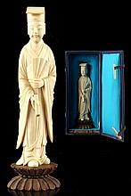 A Chinese carved ivory figure of a standing scholar, early C