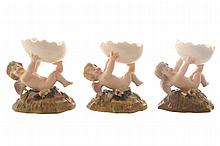 Set of eight porcelain cherub-supported quail egg stands