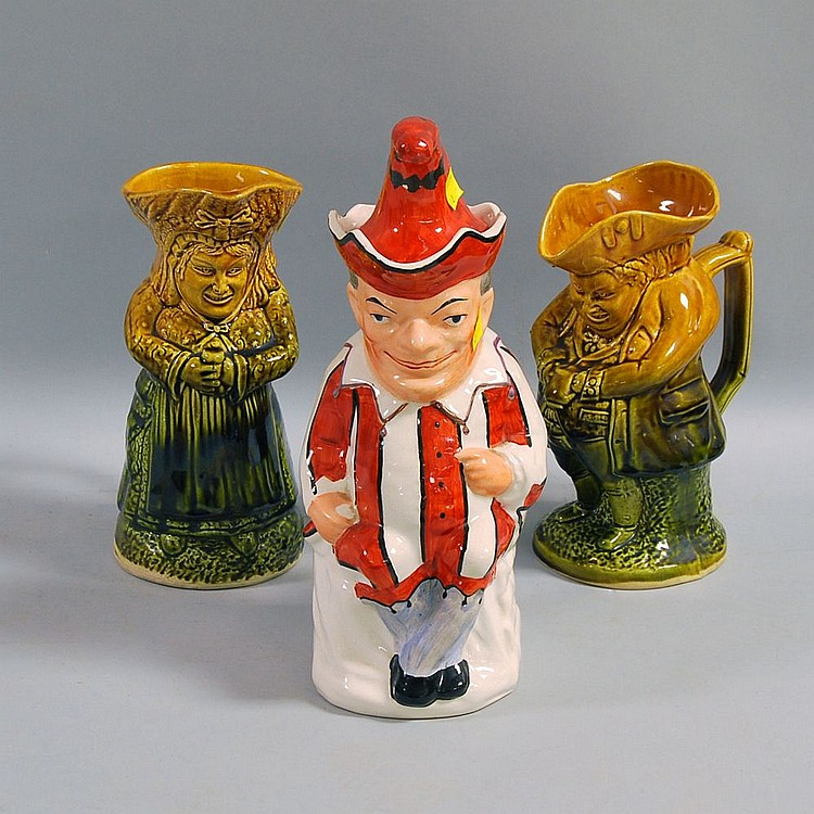 Three English Staffordshire Porcelain Character Jugs, a pair of mottled brown and green glazed jugs of a man and a woman, both grasping