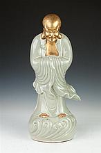 CHINESE GILT AND CELADON PORCELAIN FIGURE OF DAMO. - 20 in. high.