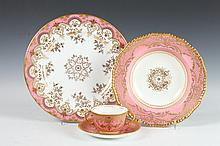49-PIECE STRAWBERRY PINK AND GILT PORCELAIN TABLEWARE, Circa 1900.