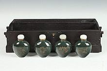 FOUR CHINESE SPINACH JADE FOUR SEASON SNUFF BOTTLES IN FITTED BOX, Qianlong mark. - 3 1/8 in. high.