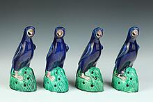 FOUR CHINESE BLUE, GREEN AND AUBERGINE PORCELAIN FIGURES OF PARROTS. - 9 in. high.