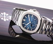 PATEK PHILIPPE | A LARGE STAINLESS STEEL AUTOMATIC WRISTWATCH WITH DATE, MOON PHASES, POWER RESERVE AND BRACELET <br />REF 5712 MVT 3171296 CASE 4370302 NAUTILUSMADE IN 2006