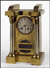 GERMAN BRASS AND COLUMN FORM GLASS MANTLE CLOCK.