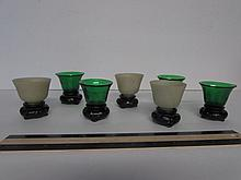 SAKE DRINKING SET THREE  OPAQUE GLASS AND FOUR GREEN GLASS SAKE CUPS ON WOOD STANDS, 2.5