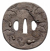 A ROUND IRON TSUBA, 19TH CENTURY carved in high