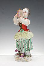 A MEISSEN PORCELAIN FIGURE OF A CHILD GARDENER PLAYING A TAMBOURINE