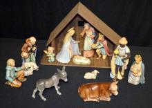 13-Piece Goebel Hummel Nativity Set in Color: 1.) Virgin Mary #214A; 2.) Baby Jesus #214A; 3.) Joseph #214B; 4.) Goodnight Angel #214C; 5.) Shepherd Standing with Sheep #214F; 6.) Shepherd Kneeling #214G; 7.) Donkey #214J; 8.) Ox #214K; 9.) Moorish King #214L; 10.) King Kneeling on One Knee #214M; 11.) King Kneeling with Cash Box #214N; 12.) Lamp #214O; 13.) Wooden Stable. Stable is 10 1/4