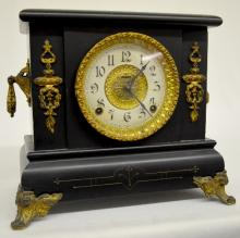 Antique Ingraham Wooden Mantel Clock: T&S with a signed paper chapter ring dial with a patterned metal center and an unsigned movement. In a black enamel wood case with metal ornaments and the pendulum. Not tested. 11