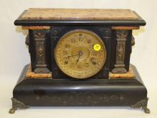 Antique Seth Thomas Mantel Clock: T&S w/unsigned patterned metal dial & signed movement. In a black enamel case with faux dark caramel marble accents, metal mask columns & metal ornaments. Not tested. 11