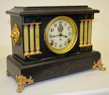 Seth Thomas Automatic 8 Day Long Alarm Clock: T & S with alarm, with a signed metal dial, a paper label, a signed movement in a case with 6 celluloid 1/2 columns. The key and pendulum are with the clock.