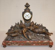 Antique French Statue Clock: T & S with a decorated porcelain dial; the movement is numbered 18773. The red marble base stands on bun feet and has 2 lovely spelter ladies lying in front of a tombstone style clock. Not tested. 20 1/2