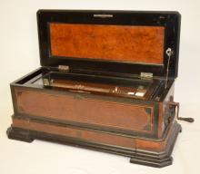 Antique Cylinder Music Box with Three Easy Change Cylinders: Single comb in a beautiful case with burl wood style panels and ebony trim.