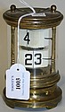 A 20th Century brass ticket clock, the glazed